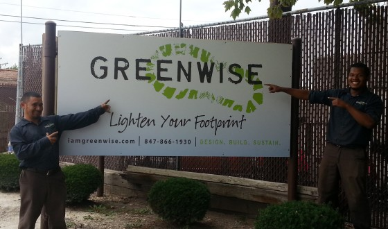 Jose and Dion point out the new Greenwise Organic Lawn Care sign on Main Street, Evanston.